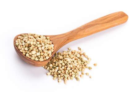 Raw buckwheat and wooden spoon on white background. Zdjęcie Seryjne