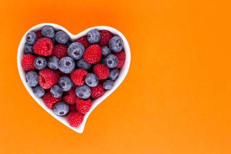 Blueberry and raspberries, fruit in a heart shaped dish on a porcelain bowl pastel Banco de Imagens