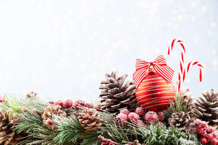 Christmas and New Year holidays bokeh background. Christmas Decoration Banner - Snowy Pine Cones On Fir Branch With Christmas Lights. Christmas bokeh background with snow fir tree. Top view with copy space for your text.