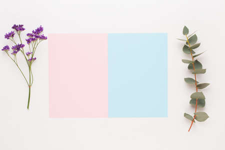 Flowers composition. Paper blank, flowers, eucalyptus branches on pastel  background. Flat lay, top view, copy spaceFlat lay stiil life.