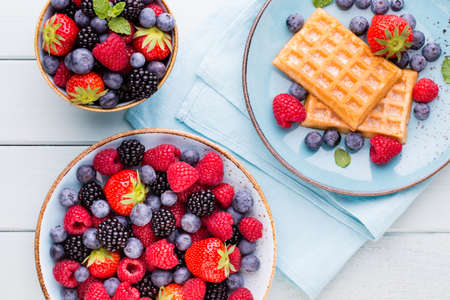 Fresh berries salad in a plate on a  wooden background. Flat lay, top view, copy space. Stockfoto