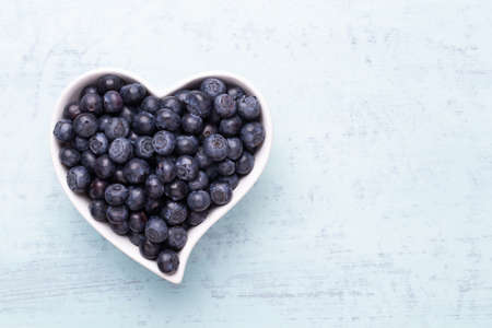Fresh blueberries, in a heart shaped bowl on a wooden background. Stockfoto