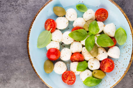 Cherry tomatoes, mozzarella cheese, basil and spices on gray slate stone chalkboard. Italian traditional caprese salad ingredients. Mediterranean food. Stockfoto