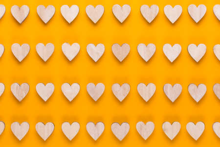 Small wooden hearts on a yellow background. A creative idea. Valentine day greeting card.