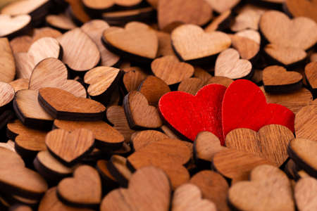 Background of wooden hearts,  red heart.  A lot of decorative wooden hearts as a festive background.