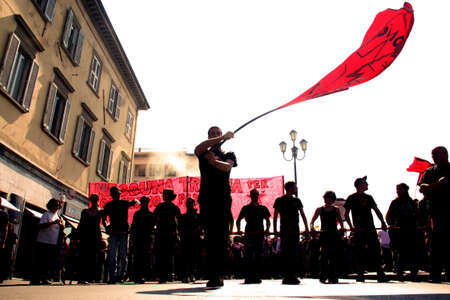 protesters: Pisa, Italy - May 6, 2011 - Activist holding a flag during the manifestation for the general strike