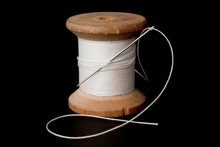 black and white sewing: Spool of white thread and a needle over a black background