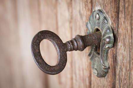 to lock: Close-up foto de una vieja llave oxidada dentro de un ojo de la cerradura