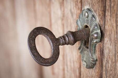closet door: Close-up shot of an old rusty key inside a keyhole