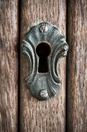 Close-up shot of a  weathered keyhole on a wooden door photo