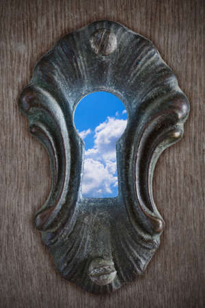 screw key: View of a partly cloudy sky through a keyhole