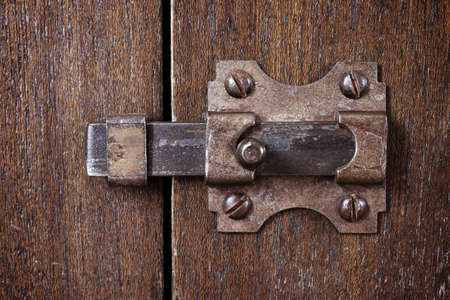 burnished: Close-up shot of an ancient latch on a wooden door