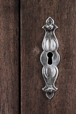 screw key: Close-up shot of a  scratched keyhole on a wooden door