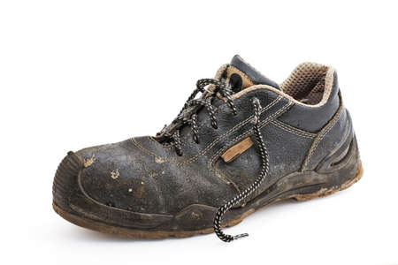 old shoes: Single worn work shoe on a white background