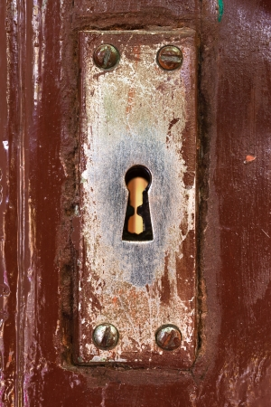 Close-up shot of a scraped keyhole on a wooden painted door photo