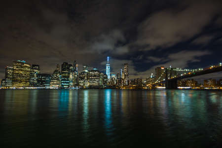 freedom tower: New York by night: Lower Manhattan and the Brooklyn Bridge as seen from Brooklyn side, in the center of the picture the One World Trade Center (Freedom Tower)