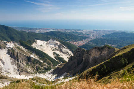 carrara: Panoramic view of Carraras marble quarries on the Alpi Apuane in Tuscany, Italy. On the backround there are the towns of Carrara (right side) and Massa (left side).