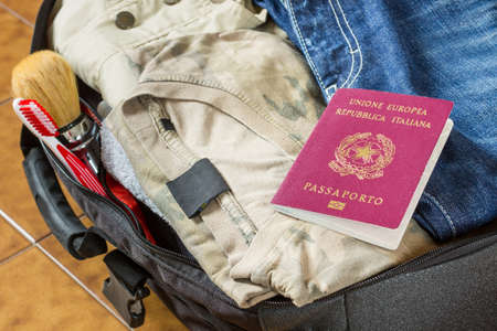 open suitcase: An open suitcase with clothes, personal effects and an italian passport on it Stock Photo