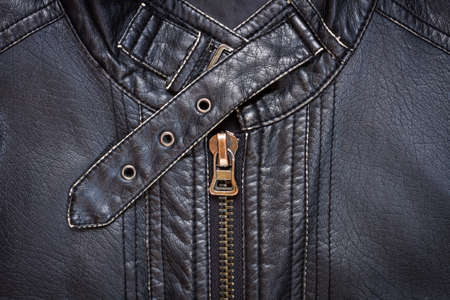 leather belt: Close-up of black synthetic leather jacket showing a zipper and a collar belt