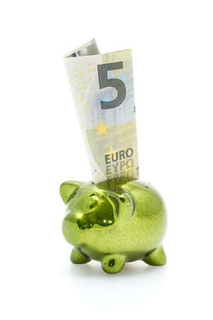 inserted: Little green piggy bank with five euro banknote inserted
