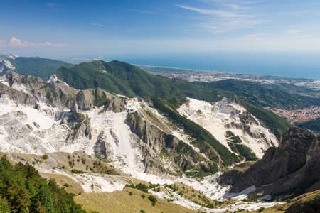 carrara: Panoramic view of Carraras marble quarries on the Alpi Apuane in Tuscany, Italy. On the backround there are the towns of Carrara and Massa.