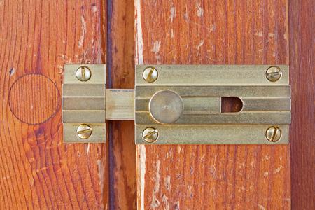 deadbolt: Close-up frontal shot of a latch on a wooden door Stock Photo