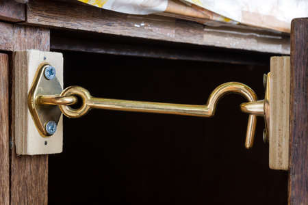 closet door: Metallic gold chromed hook with eye fixed on a closet holding the door