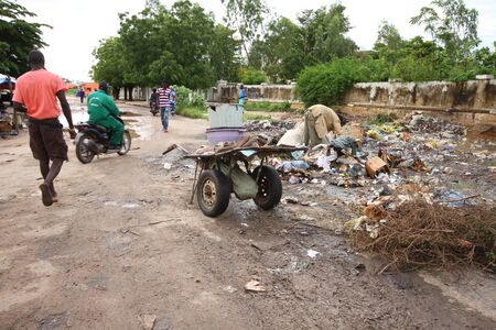 third world: Kaolack, Senegal - September 03, 2012: Peoples and garbage in a street of Kaolack in Senegal, a poor man is looking for something in the stack of garbage. Editorial