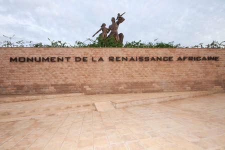 french renaissance: Dakar, Senegal - August 31, 2012: In the foreground the wall with the french writing and in the background the 49 meter tall bronze statue named African Renaissance Monument. Editorial