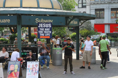 preach: Manhattan, New York, USA -  May 26, 2015: People in Union Square near the subway entrance, a man is holding a poster in order to moralize.