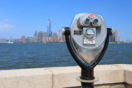 wtc: New York, USA -  May 30, 2015: Binoculars in Ellis Island pointed towards Manhattans skyline in a sunny day. Editorial