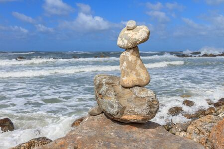 mare agitato: Rock balancing over a cliff on a shore near the rough sea Archivio Fotografico