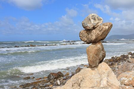 mare agitato: bilanciamento roccia verticale sopra una scogliera su una riva, vicino al mare agitato