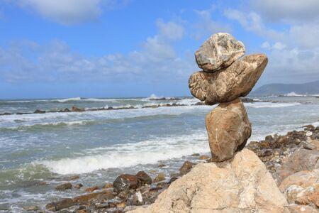 rough sea: Vertical rock balancing over a cliff on a shore near the rough sea