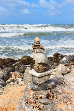 mare agitato: Roccia che equilibra sopra una scogliera su una riva, vicino al mare agitato