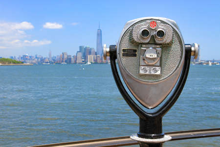 manhattans: New York, USA -  May 30, 2015: Binoculars in Ellis Island pointed towards Manhattans skyline in a sunny day. Editorial