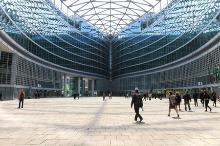 modern architecture: Milan, Italy - April 18, 2016: People walking in the indoor square of Palazzo Lombardia, a complex of building in the centre of Milan.