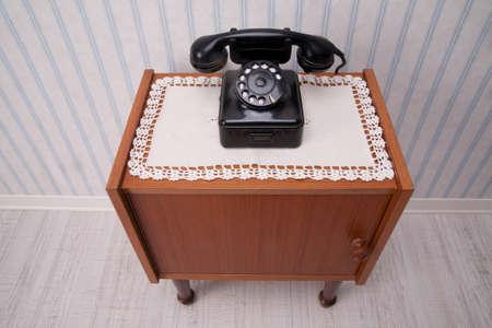 rotary dial telephone: Tel�fono Negro dial giratorio en un mueble con el viejo papel pintado a rayas de moda Foto de archivo