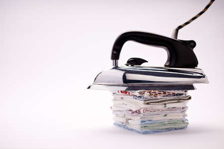 handkerchiefs: old fashioned electric iron with a black plastic handle and steel base lain on a pile of handkerchiefs in a natural light background Stock Photo