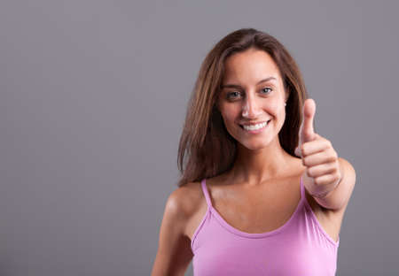 Mediterranean beautiful girl smiling and expressing positivity with her OK thumbs up photo