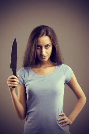 Unsettling dark young woman holding a dengerous knife in his hand photo