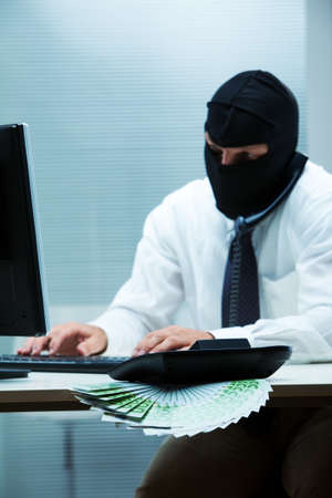 desk clerk: A desk clerk wearing a balaclava while doing some swindle about money  focus on the money