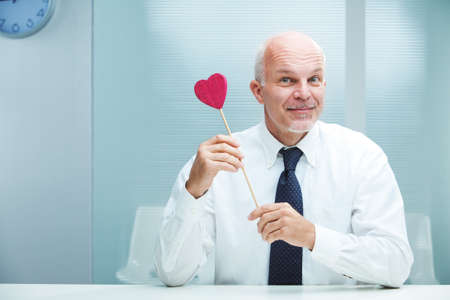 Smiling handsome businessman offering his love Stock Photo