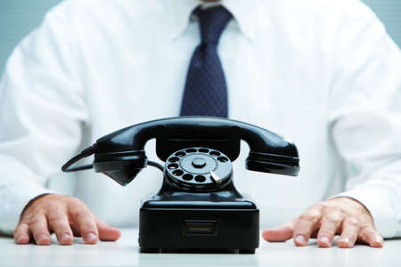 black telephone on focus with a business waiting for a call on the background photo