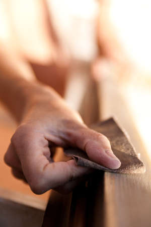 Hands of a woman with sandpaper doing DIY work on wooden fixtures Stock Photo