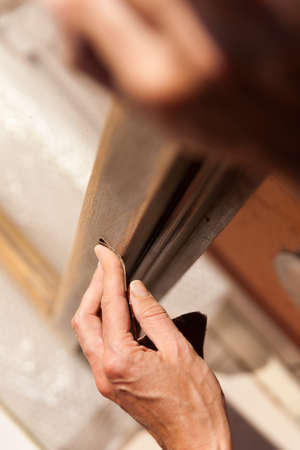 Hands of a woman with sandpaper doing DIY work on wooden fixtures photo