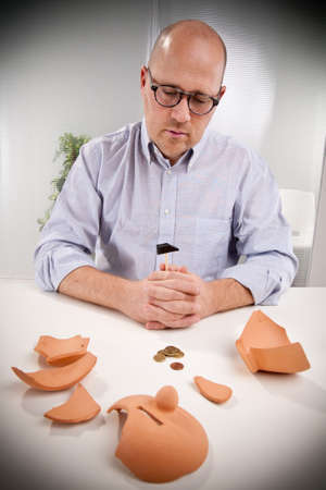 an office worker observes sadly that there are no more money left even after breaking the piggy bank. We are in deep shit. Stock Photo