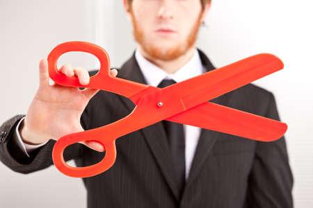ein junger Geschäftsmann, der eine große rote Schere Standard-Bild