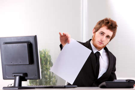 imposing: Businessman imposing a document on you with a neutral expression Stock Photo