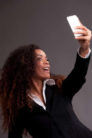Beautiful afroamerican woman smiling at her phone shooting a selfie photo